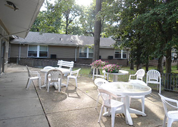 Eagleview patio area with white chairs and tables surrounded by flowers and trees