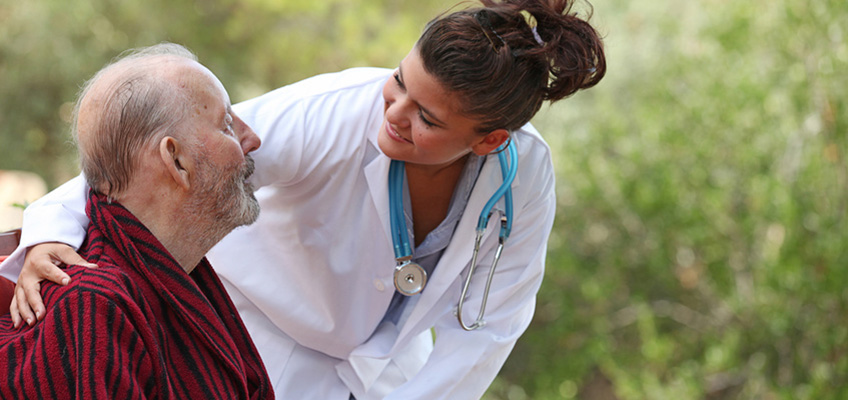 doctor leaning down to speak with a resident seated outside