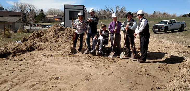Ground breaking day with staff members digging in the dirt with hard hats on