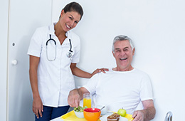 nurse standing beside a resident in bed with a tray of food for breakfast
