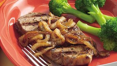 Pepper-Rubbed Grilled Steaks with Caramelized Onions