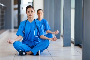 two young healthcare workers meditation during break to release work pressure