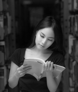 A portrait of a mixed race college asia student at campus in library and read a book