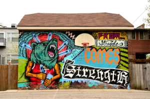 "This mural was painted by artist Sentrock on a garage in North Lawndale. Titled ""From Struggle Comes Strength,"" it embodies the spirit of the neighborhood. (Credit: Tiffany Huang)"
