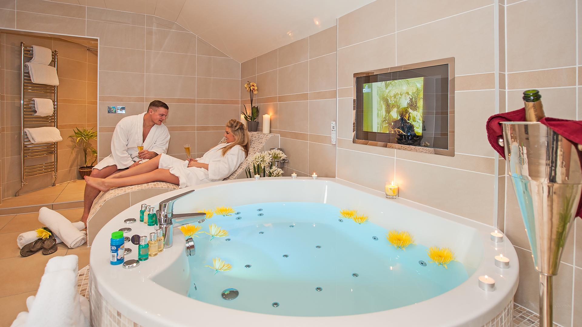 Couple in Bathrobes Beside Giant Luxury Hotel Spa Bath