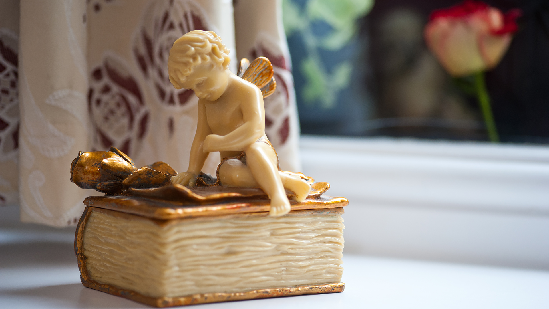 Room Decor: ornament of angel reading on a pottery book