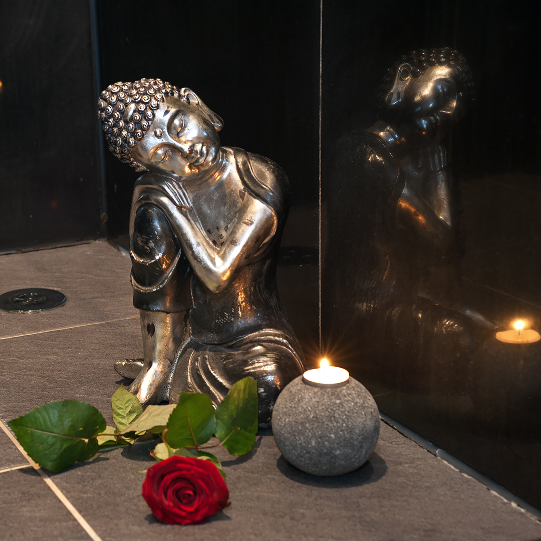 Amaryllis room detail Small bronze statuette of Asian deity, rose and scented candle