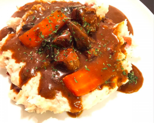 Beef and Guinness stew, plated with mashed potatoes