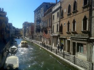 A boat rushing through the still waters of Venice Canals.