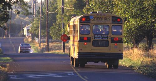 Photo of school bus driving in neighborhood.