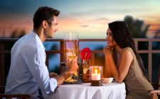 a couple enjoying a candlelit dinner overlooking a lake