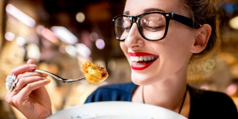 a woman, smiling, as she eats a plate of pasta