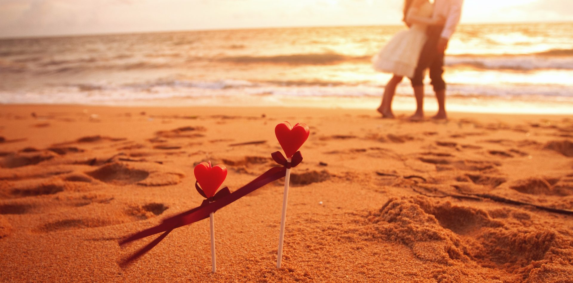 couple on the beach with two heart sticks in the sand at St Lucia