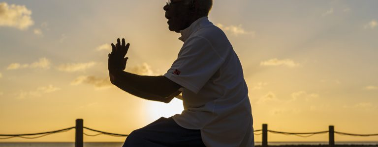 man dancing on boardwalk with sun setting behind him in St Lucia