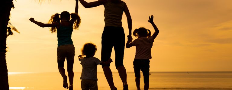 mother and kids jumping on the beach in front of sunset in St Lucia