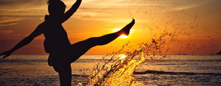 woman kicking water with sunset behind her in St Lucia