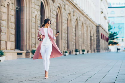Business woman walking and texting