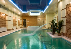 Beautiful indoor swimming pool design with neon ceiling lighting and hot tub