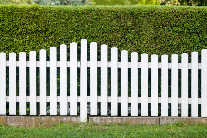 This wave-design white fence features posts at multiple heights, over concrete base, in front of neatly pruned bush wall.