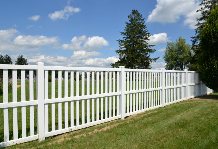 Sparse post design on this white fence bookended and tied at the middle with horizontal wood beams.