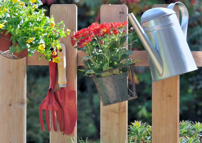 Garden fence design features sparse, widely spaced posts with hooks for gardening tools.