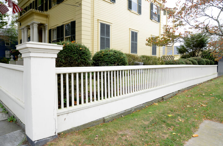 Here's a low slung white fence with cylindrical posts sandwiched between thick horizontal beams, with large square posts at corners.