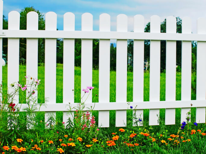 Traditional white picket fence with rounded post tops.