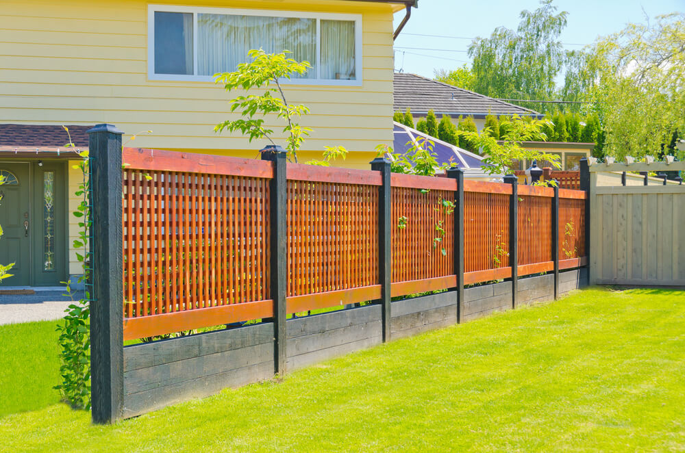 modern lattice fence comprised of black stained wood posts and base with lighter red toned