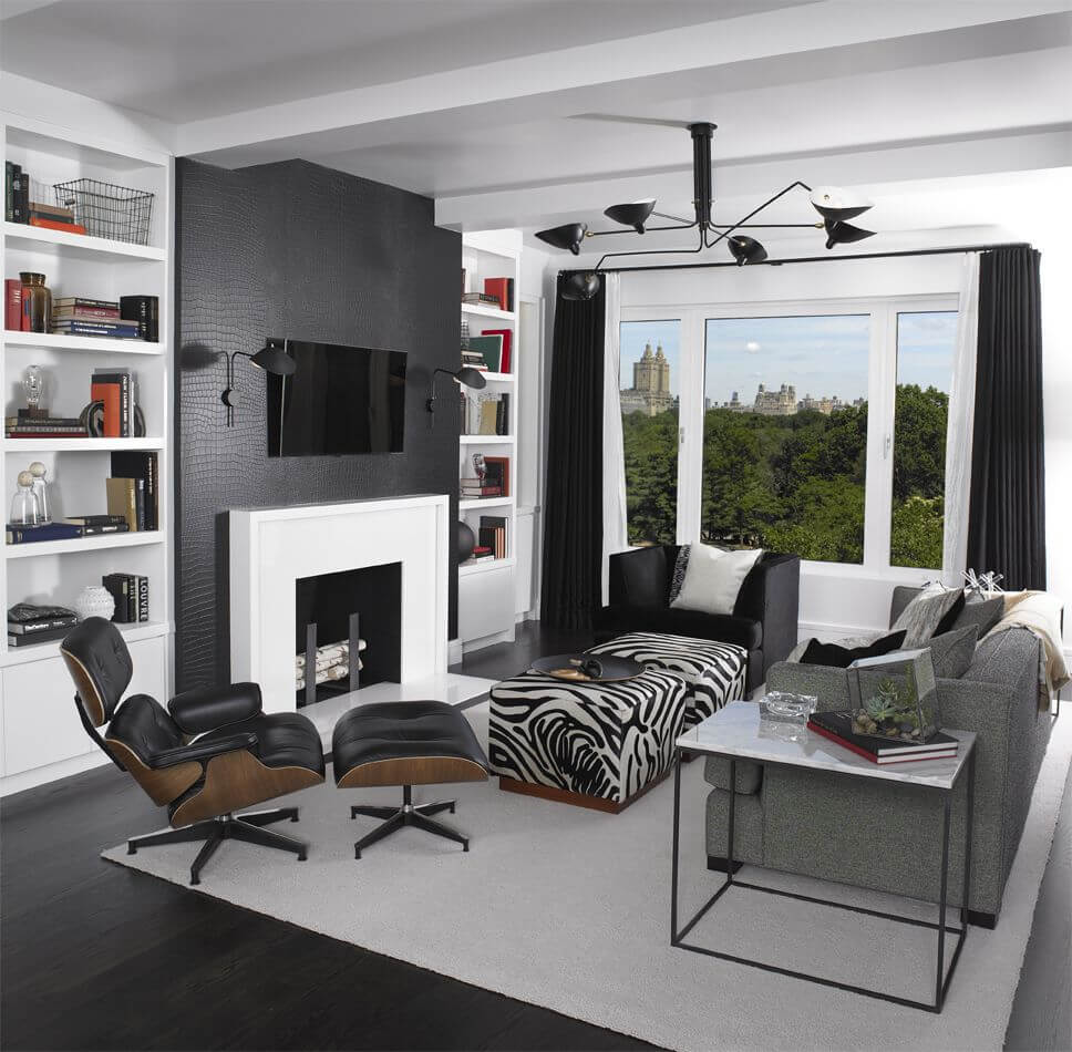High contrast black and white living room features mixture of furniture styles, including zebra print twin square ottomans with hardwood base at center.