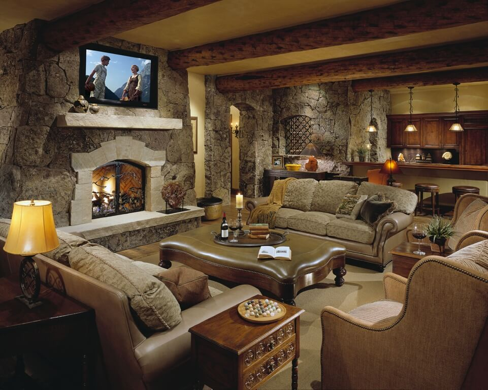 Stone walls and exposed wood beams give this living room a truly rustic look. Rolled arm sofas face off over ornate carved wood ottoman coffee table with brown leather cushion surface, nail head trim, and carved arrow feet.