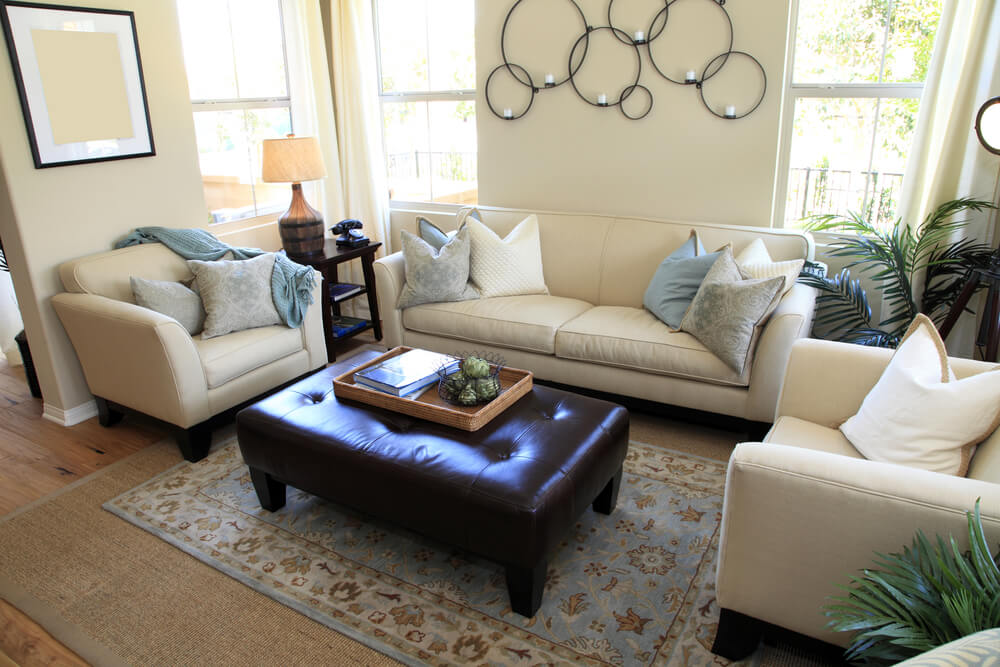 Cozy white living room with natural hardwood flooring and linen upholstered seating is centered around large bench style button tufted brown ottoman.