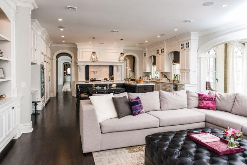 Ornate, open white space shares kitchen and living room, featuring L-shaped sectional grey couch on patterned rug, centered around large square button tufted leather ottoman.