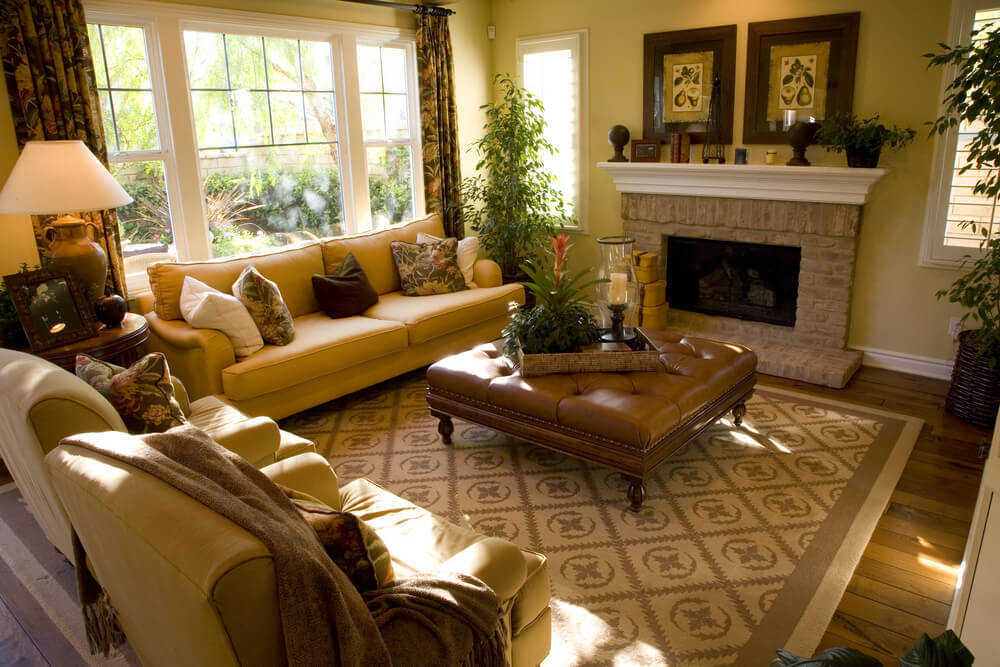 Warm golden hues throughout this natural hardwood floored living room, with pair of matching armchairs and lengthy sofa wrapped around large square brown button tufted ottoman, featuring dark carved wood structure and arrow feet.