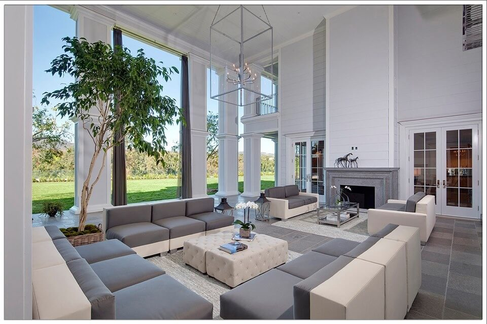Immense, two story living room in grey and white tones, featuring wrap around two-tone sectional sofas, encircling beige button tufted leather bench ottomans.