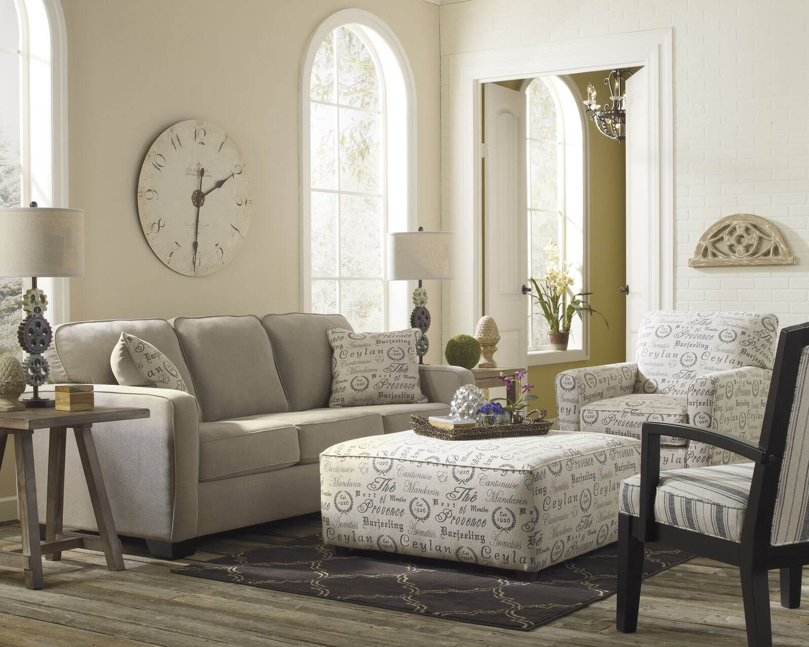 Light toned living room stands over grey hardwood flooring, with neutral grey sofa next to text-patterned white armchair and matching square cushion ottoman.