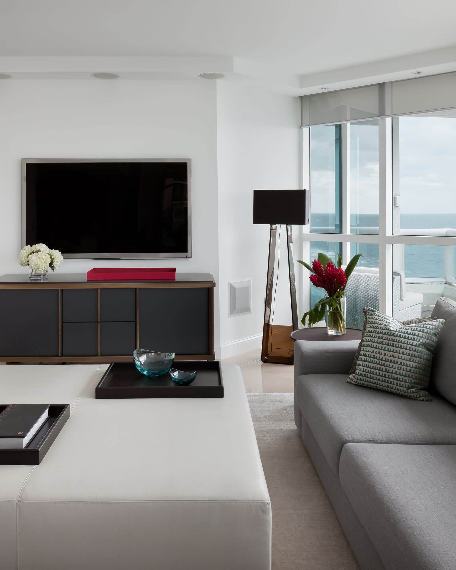 Slick textures in this modern living room include minimalist wood media center and off-white leather square ottoman with twin dark wood removable table surfaces.
