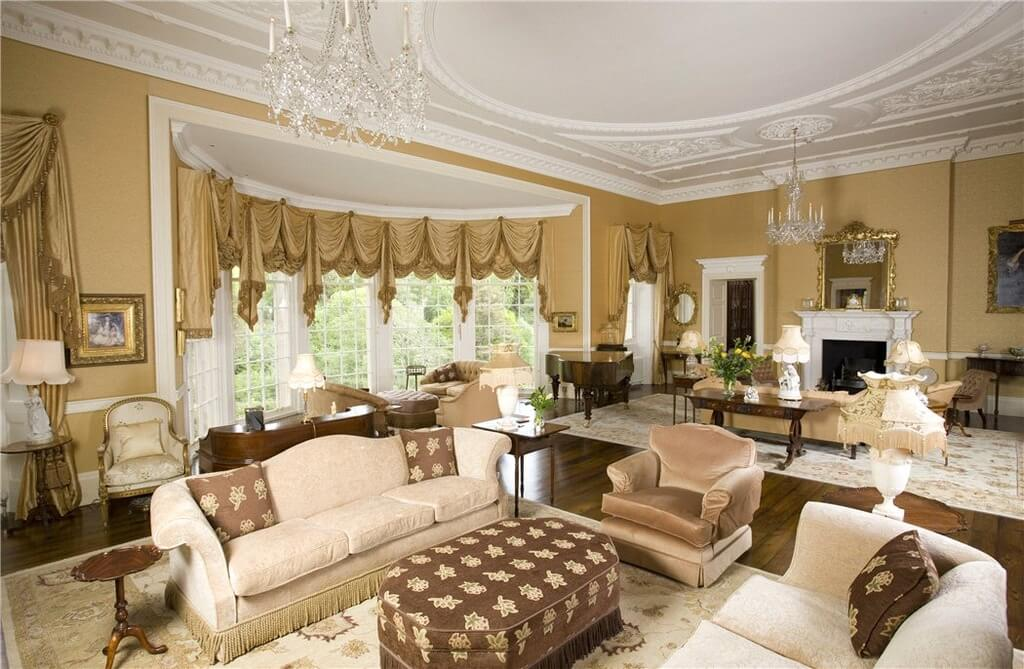 Ornate gold and white living room features expanse of rounded floor to ceiling windows to light this open space featuring multiple furniture sets, with patterned fabric octagonal ottoman at center.