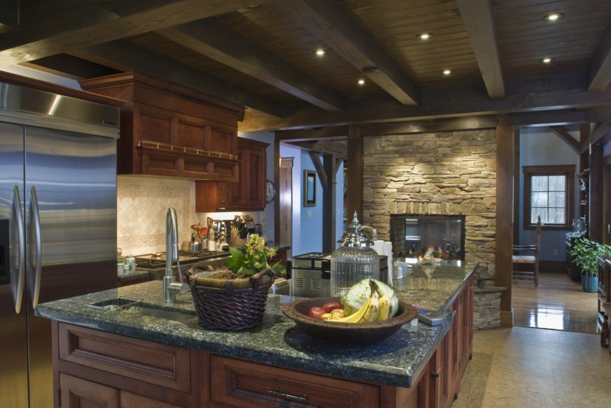 Beautiful kitchen with stone fireplace and dark cabinetry with dark wood ceiling.
