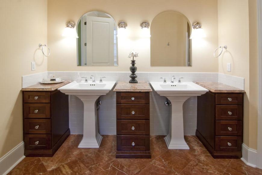 Bathroom with pedestal sinks and free-standing vanities.