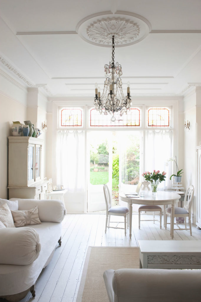 A Light Living Room Area With White Linen Couches And French Doors That  Lead Out Into