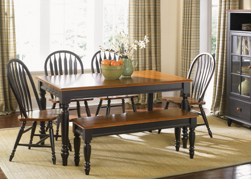 this rich high contrast table features natural wood tone surface and dark painted legs