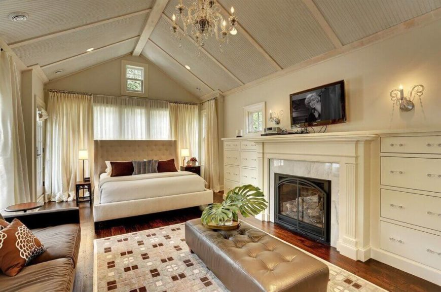 flat screen tv on wall over fireplace. this luxurious bedroom has a marble hearth on the fireplace for touch of deluxe taste flat screen tv wall over