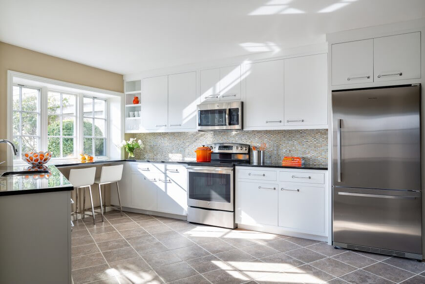 bright and open design informs this kitchen flush with white cabinetry and stainless steel appliances