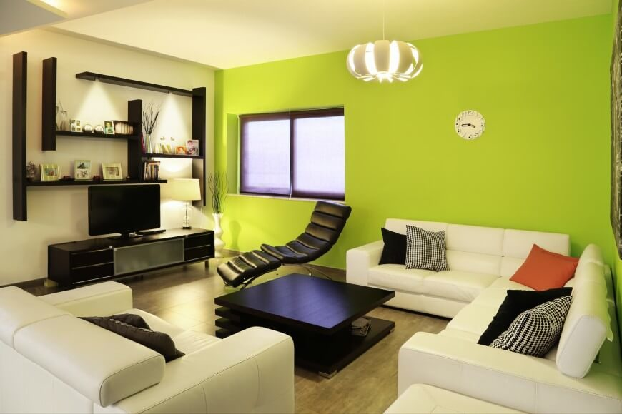 this modern living room uses a vibrant accent wall and a singular color pillow to add