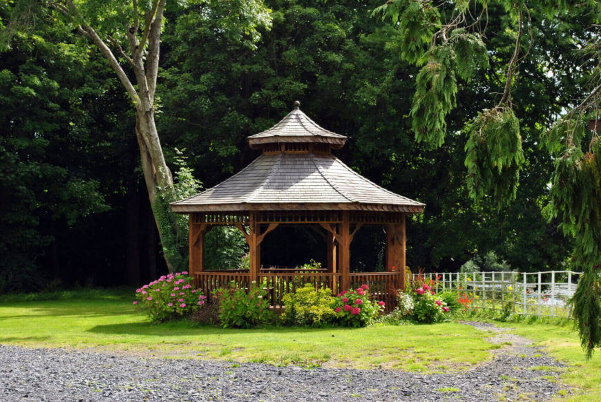 At the end of this stone path sits a lovely octagonal gazebo surrounded by flowers. Adding flower bushes around a gazebo is a perfect way to blend the structure into the rest of your landscaping.