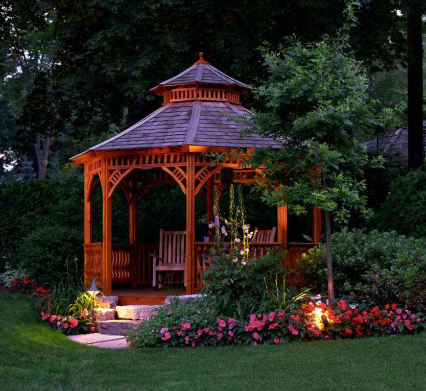 This gazebo is a marvelous example of a gazebo garden. It uses a combination of pink and purple flowers with different lighting fixtures to liven up the structure.