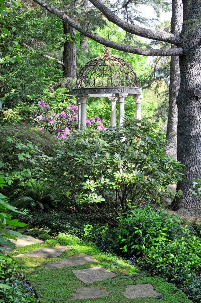 This ornate and decorative gazebo sits in the woods and presents great design elements. The detailed iron work of the top meshes well with the natural lines of the plants.