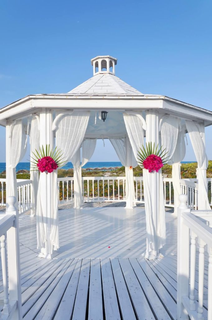 These flower bouquets are wonderful enhancements to the pillars of this gazebo. They provide an amazing contrast and visual appeal to the stark white pillars and curtains.