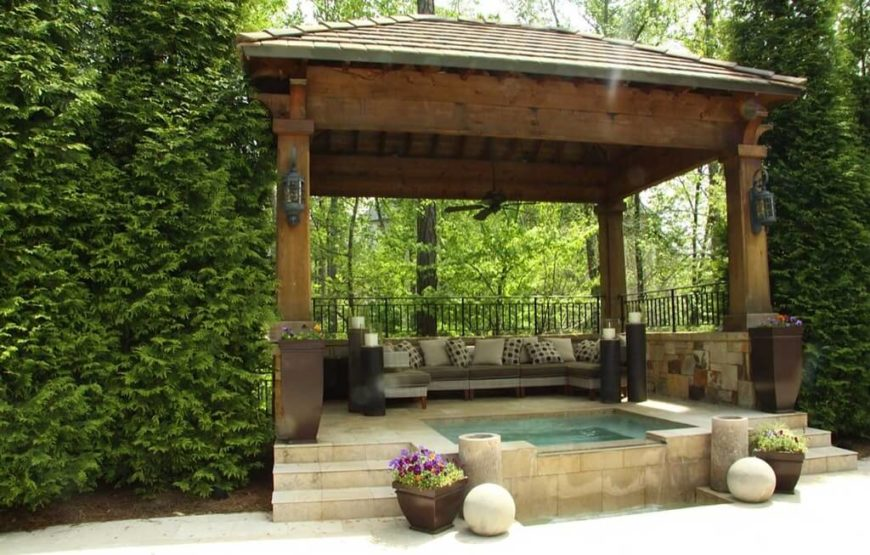 this fabulous gazebo houses not only a lovely stone hot tub but a set of patio