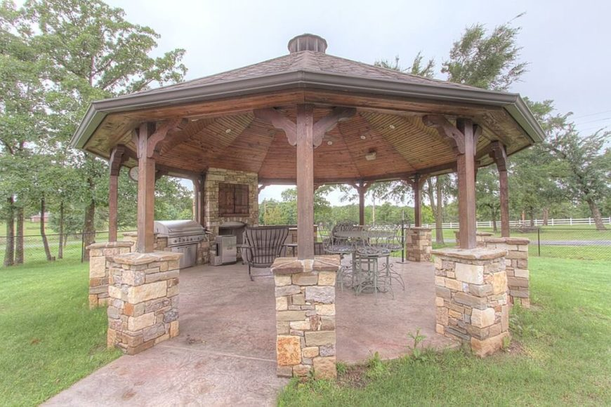This large stone and wood gazebo features a fireplace, dining space, and a large stainless steel grill.